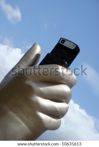 Giant hand sculpture holding a slide cellphone - stock photo
