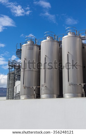 Giant industrial tanks on the bright blue sky background
