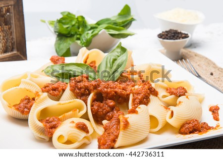 Giant macaroni with meal and green basil