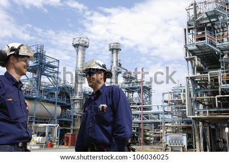 giant oil and gas fuel tanks with two workers in foreground, blue toning concept - stock photo