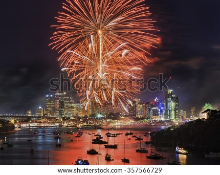 giant orange red fire balls during New Year familly fireworks in Sydney over CBD high-rises and still harbour waters - stock photo