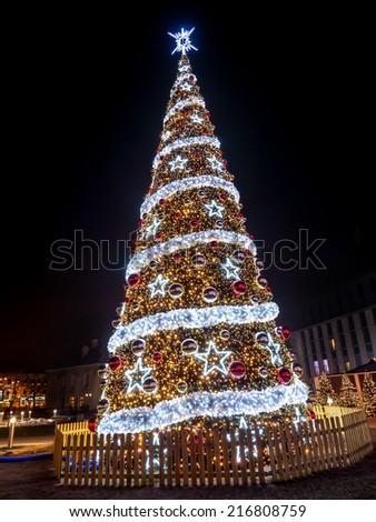 Giant outdoors Christmas tree illuminated at night - stock photo
