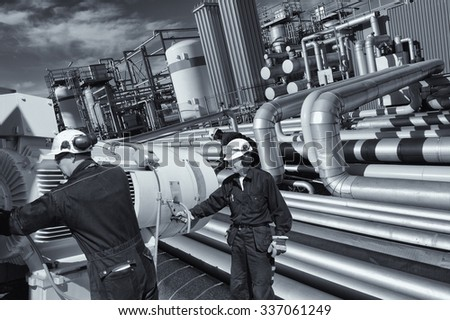 giant pipeline construction, engineer checking for leaks inside refinery - stock photo