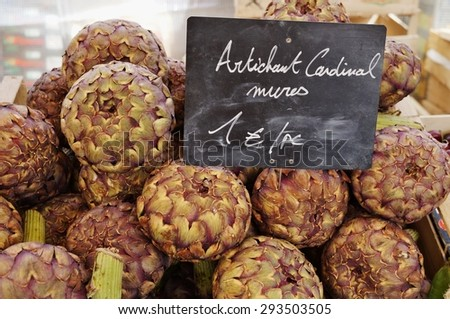 Giant purple Roscoff artichokes from Brittany, France at a farmers market - stock photo