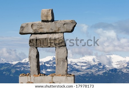 giant rock inukshuk with mountains - inuit symbol for 'the way' - stock photo