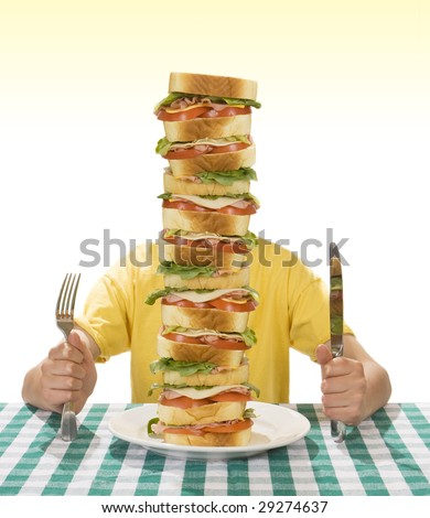 Giant sandwich on a white plate, with hands holding a a knife and fork on a table cloth. - stock photo