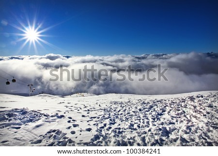 Giant sun flare shines over top of ski resort above the clouds in France - stock photo