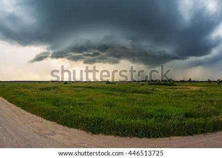 Giant supercell growing over the green field. Storm, thunderstorm, tornado,