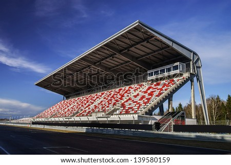 Giant tribune with colorized seats on Formula 1 track - stock photo