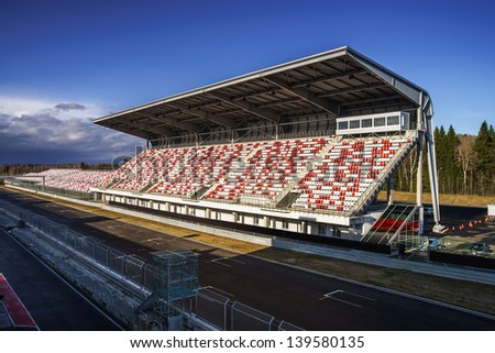 Giant tribune with colorized seats on track - stock photo