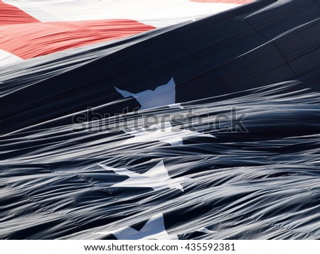 Giant USA flag unraveling puffing in the air with stars and stripes. - stock photo
