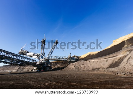 Giant wheel of bucket wheel excavator in a brown coal open pit. - stock photo