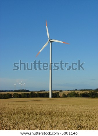 Giant wind turbine on a hilly field