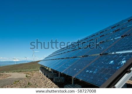 Giant wind turbines and solar panel on a mountain ridge - stock photo
