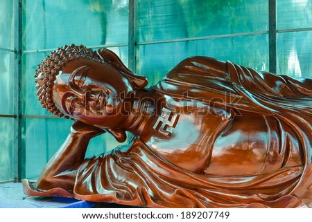 Giant Wood Carving of Laying Buddha - stock photo