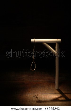 Gibbet with loop on gloomy wooden background