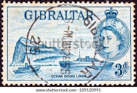 GIBRALTAR - CIRCA 1953: A stamp printed in Gibraltar shows Ocean liner, Gibraltar and Queen Elizabeth II, circa 1953. - stock photo