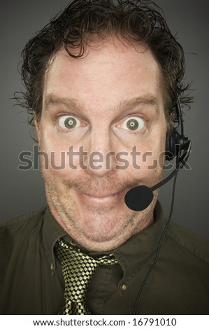 Giddy Businessman Smiles Wearing a Phone Headset Against a Grey Background. - stock photo