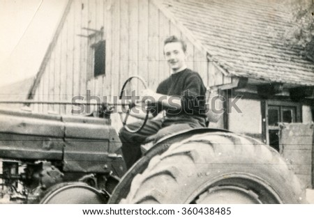 GIESMANNDORF, GERMANY, CIRCA THIRTIES - Vintage photo of young man on tractor - stock photo