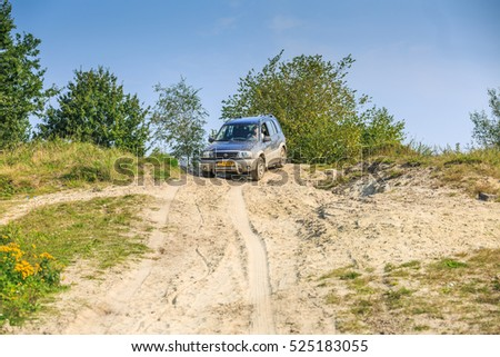 Gieten, provincie Drenthe, the Netherlands at 5 september  2014: A Suzuki Grand Vitara-2.0 drive down  over a steep Sandy slope in a sand quarry