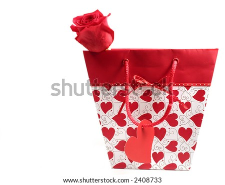 Gift bag with hearts, blank tag and red rose isolated on white