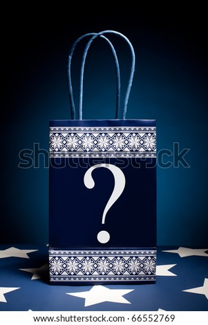Gift bag with question symbol on it. Concept - thinking about holiday gifts.
