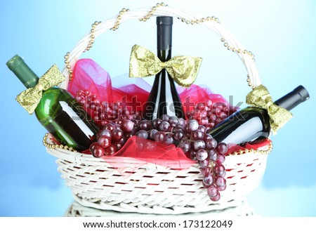 Gift basket with wine on blue background - stock photo