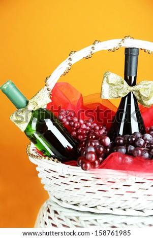 Gift basket with wine on orange background - stock photo