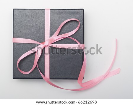 Gift black box tied with satin ribbon on gray - stock photo