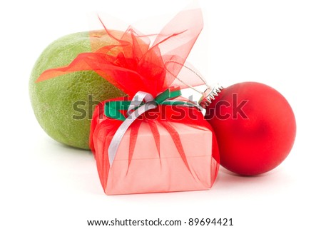 Gift box against the background of a grapefruit and a red ball - stock photo