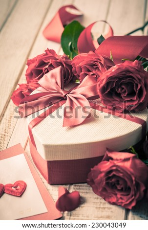 Gift box and bouquet of roses for holiday on wooden background in vintage style. Selective focus,toned image. - stock photo