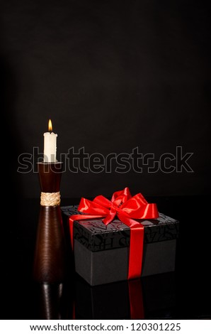 Gift box and candle against black background