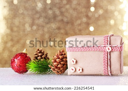 Gift box and Christmas decor on table on shiny background - stock photo