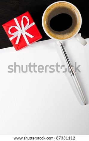 gift box and coffee cup with notepad on dark table - stock photo