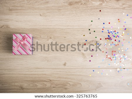 Gift box and colorful confetti on a wooden background - stock photo