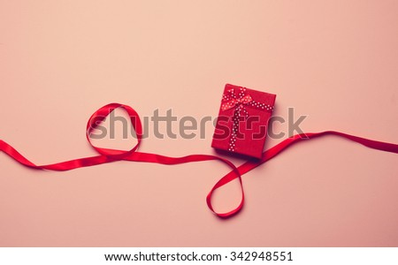 Gift box and red ribbon on pink background