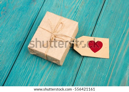 Gift box and tag with sign in the shape of heart on blue wooden table