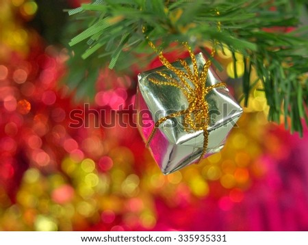 gift box Christmas ornament on pine tree branch and bokeh background. - stock photo