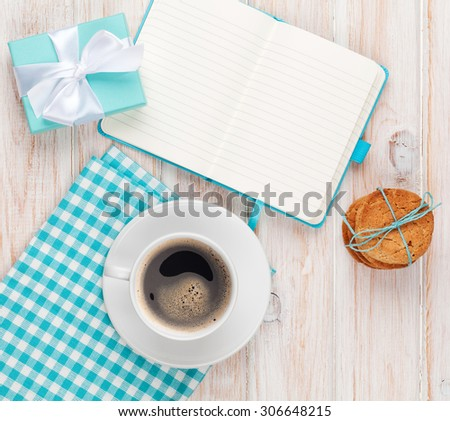 Gift box, coffee, cookies and notepad on white wooden table with copy space - stock photo