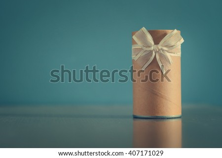 Gift box, Cylinder gift box with ribbons for Christmas, new year or celebration holidays  on blue  background, Vintage color, copy space, copyright space. - stock photo