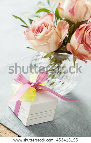 Gift box decorated with bow and roses in vase