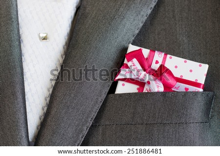 Gift box in a suit pocket. Elegance smoking. Close Up