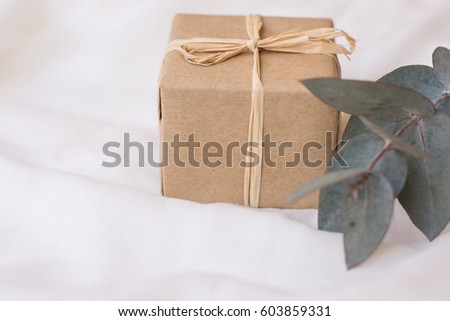 Gift box in craft paper branch of silver dollar eucalyptus on white linen fabric, minimalistic style conceptual