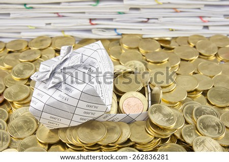 Gift box in heap of gold coins  with pile of paperwork as background. - stock photo