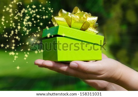Gift box in woman's hands on green phone with rays and stars