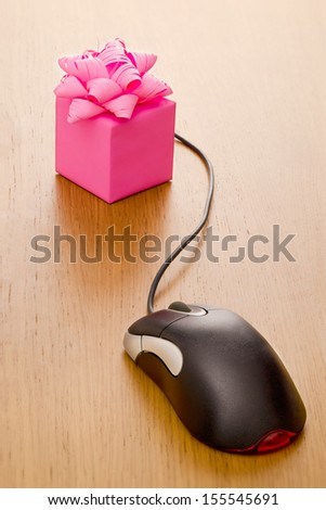 Gift box on a desk with mouse attached - stock photo