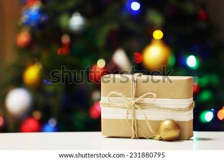 Gift box on Christmas tree lights background - stock photo