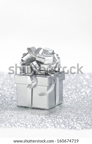Gift box on glitter silver background with white copy space - stock photo