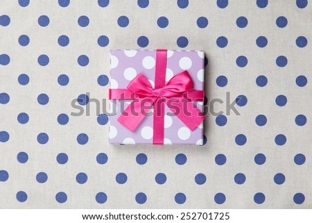 Gift box on polka dot background.  - stock photo