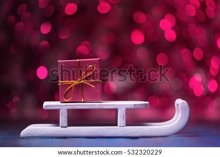 Gift box on Santa's sledge over abstract pink background